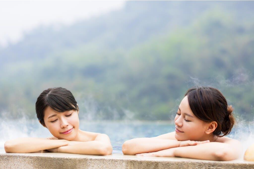 Two Japanese women enjoying a bath at an outdoor onsen.