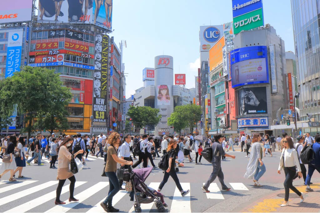People walking around Shibuya crossing during the day with the 109 building in the center background