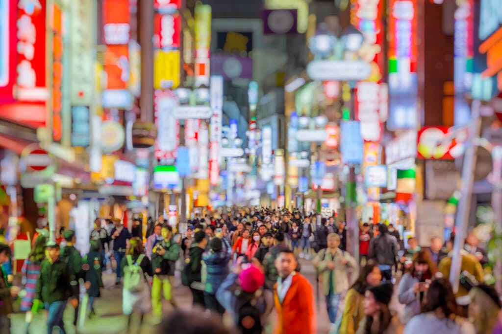 The streets of Shibuya at night with many people walking and many signs lit up