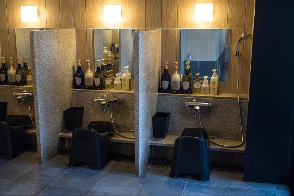 A series of stools in front of showers with mirrors and amenities at a sento