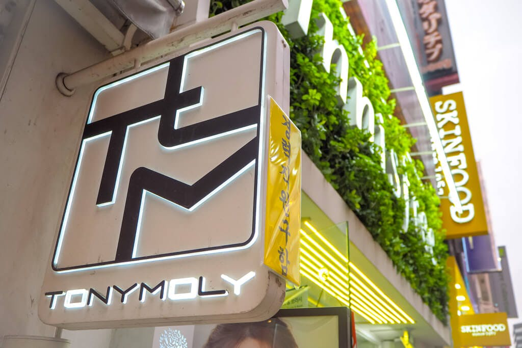 A TonyMoly sign in Japan with an Innisfree and Skinfood sign in the background.