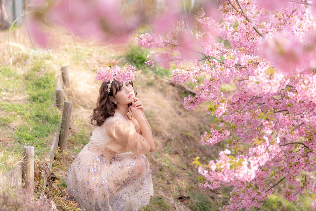 A Japanese woman takes in the beauty of cherry blossoms in a park