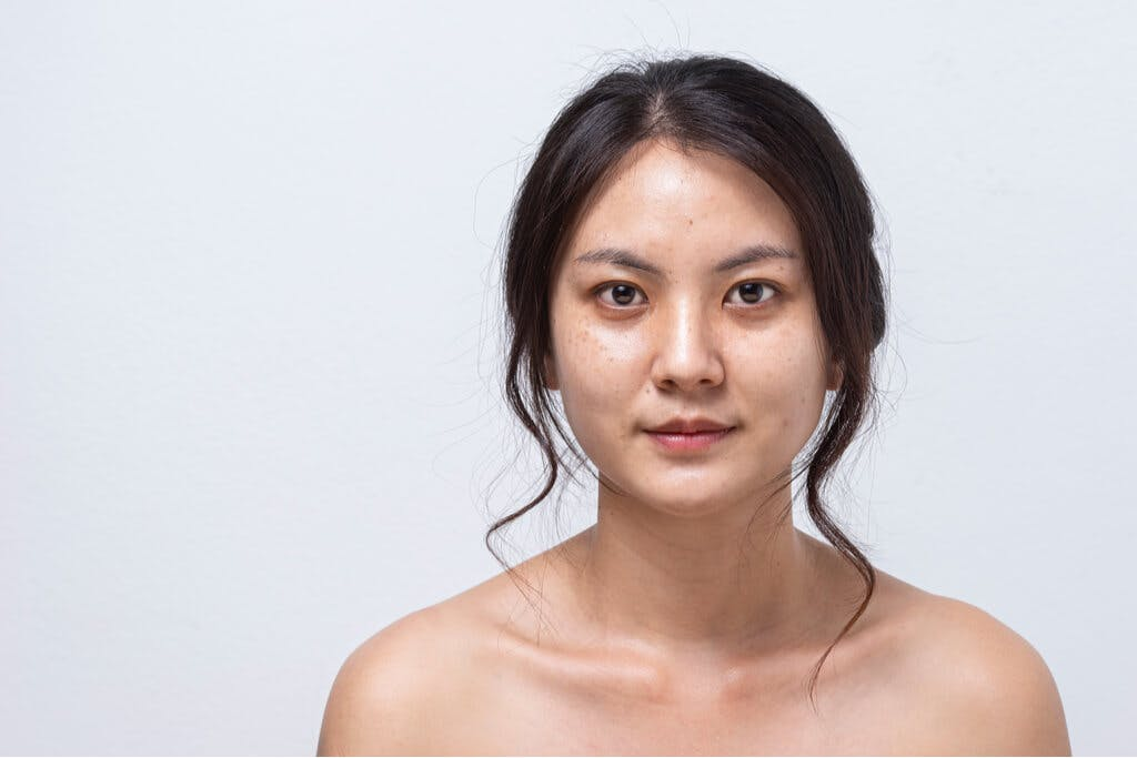 A woman stands in front of a gray background with no makeup on