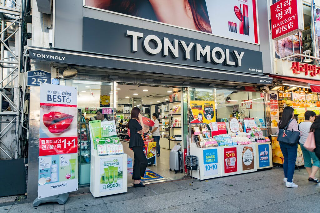 The exterior of a Tony Moly store with the doors open and people standing inside and people walking outside with several displays