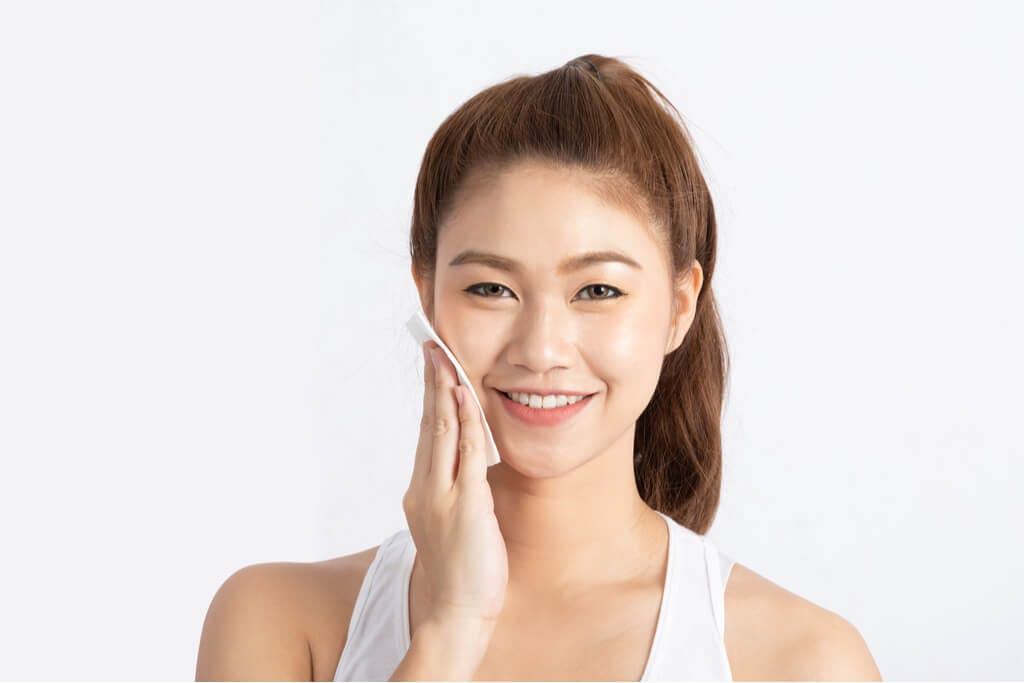 A young woman wipes Korean toner onto her face in front of a white background