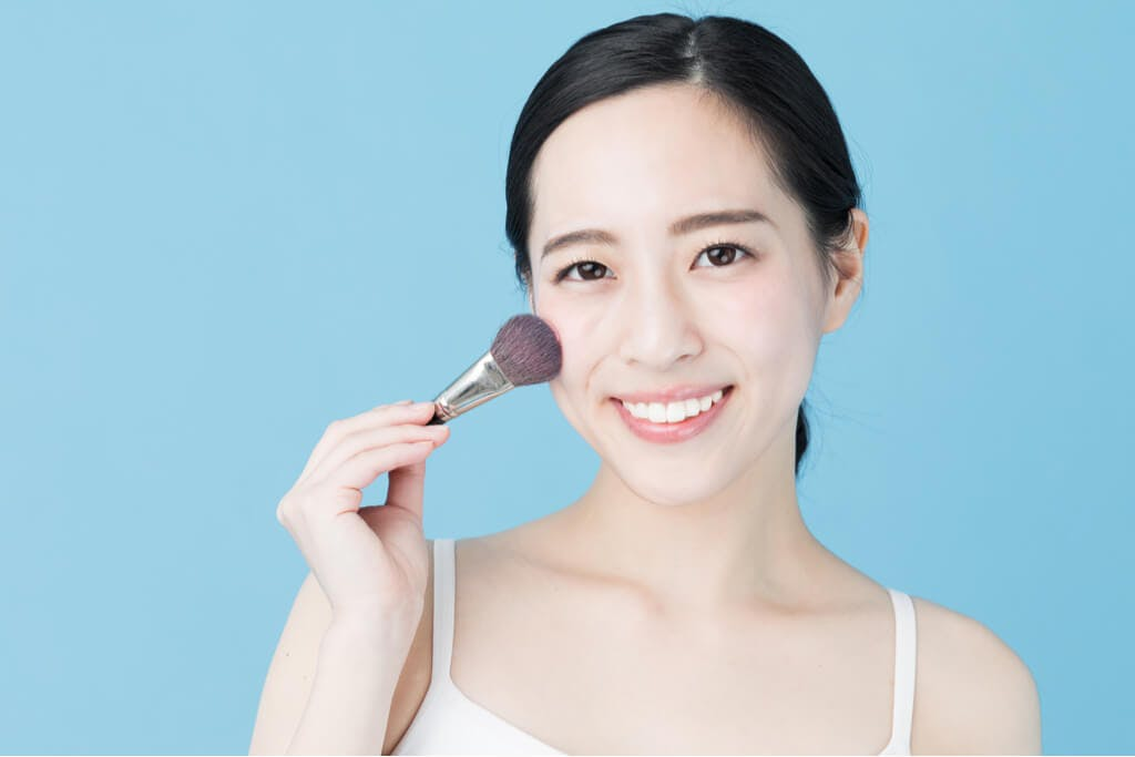 An Asian woman in front of a blue background holding a foundation brush to her skin.
