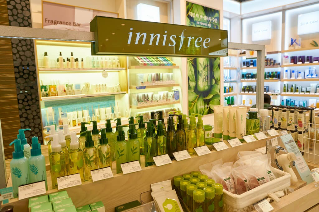 The inside of an innisfree section in a store with many green and white products.