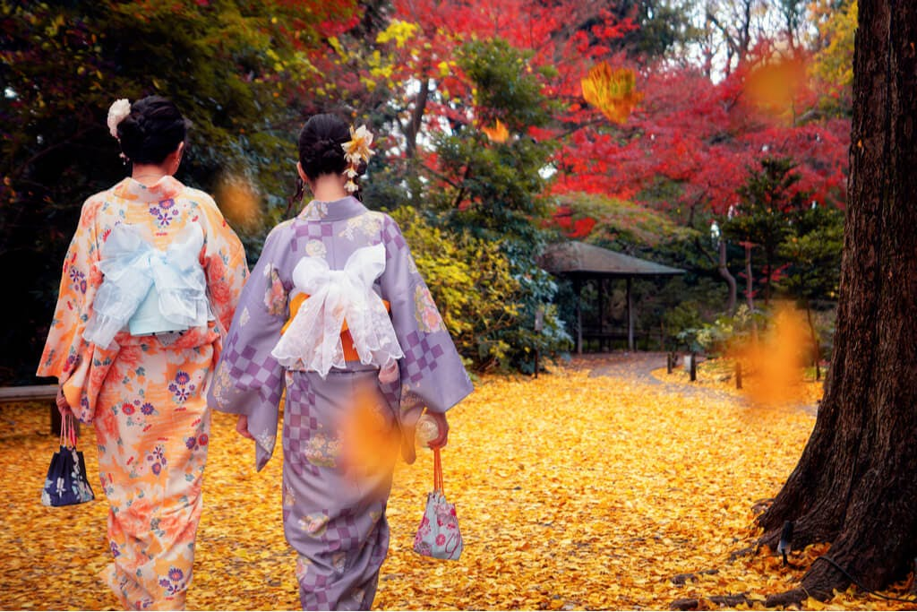 Two women in kimonos walk through a park in Tokyo with beautiful changing leaves