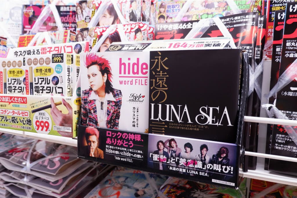 A photo of Hide in visual Kei clothing next to a book of Luna Sea.