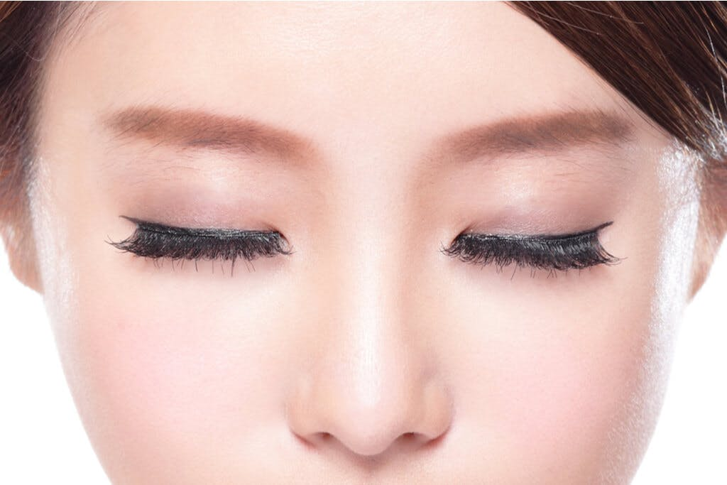 A woman with nice makeup looking down slightly with her eyes closed showcasing her eye makeup.