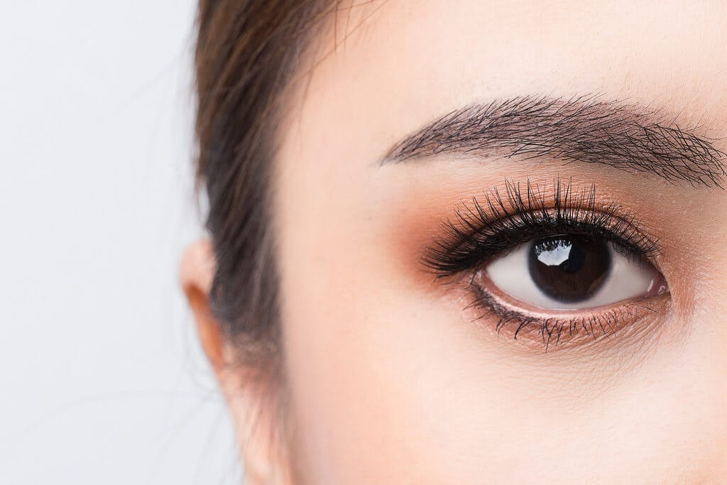 A woman's eye with long lashes and a slightly orange eye shadow