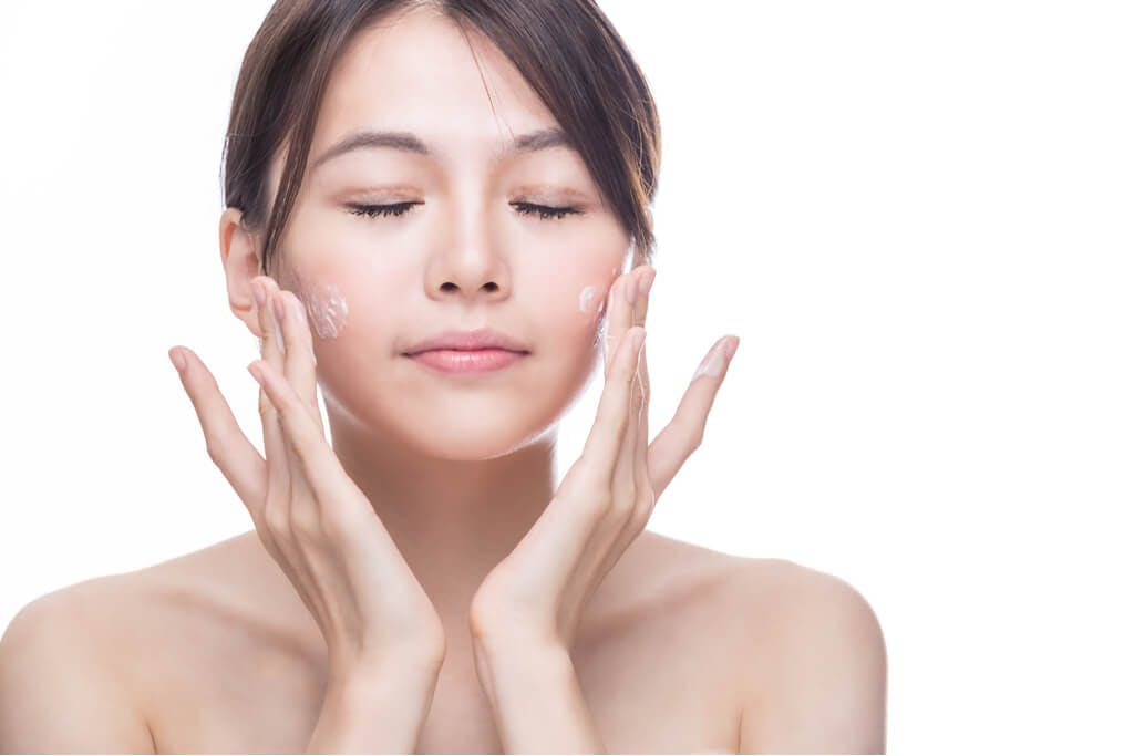 A woman rubs cream into her skin as she closes her eyes