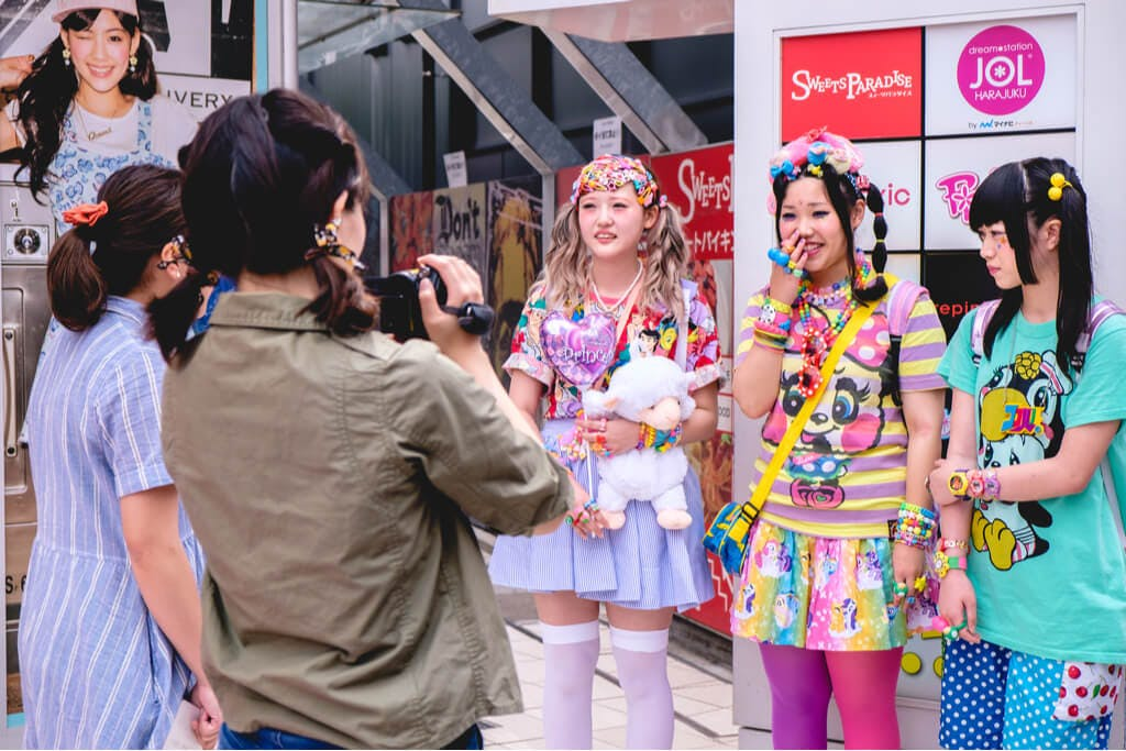 Three girls in Decora fashion being interviewed by two people in front of a Harajuku building
