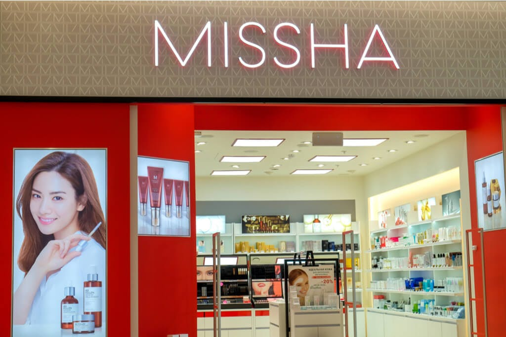 The exterior of a small MISSHA store with an ad with a woman holding a product outside