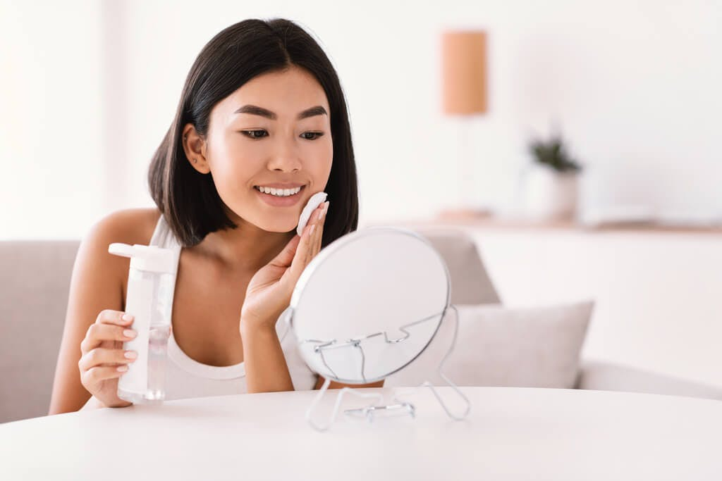 A woman sits in her white living room in front of a white mirror while putting on toner