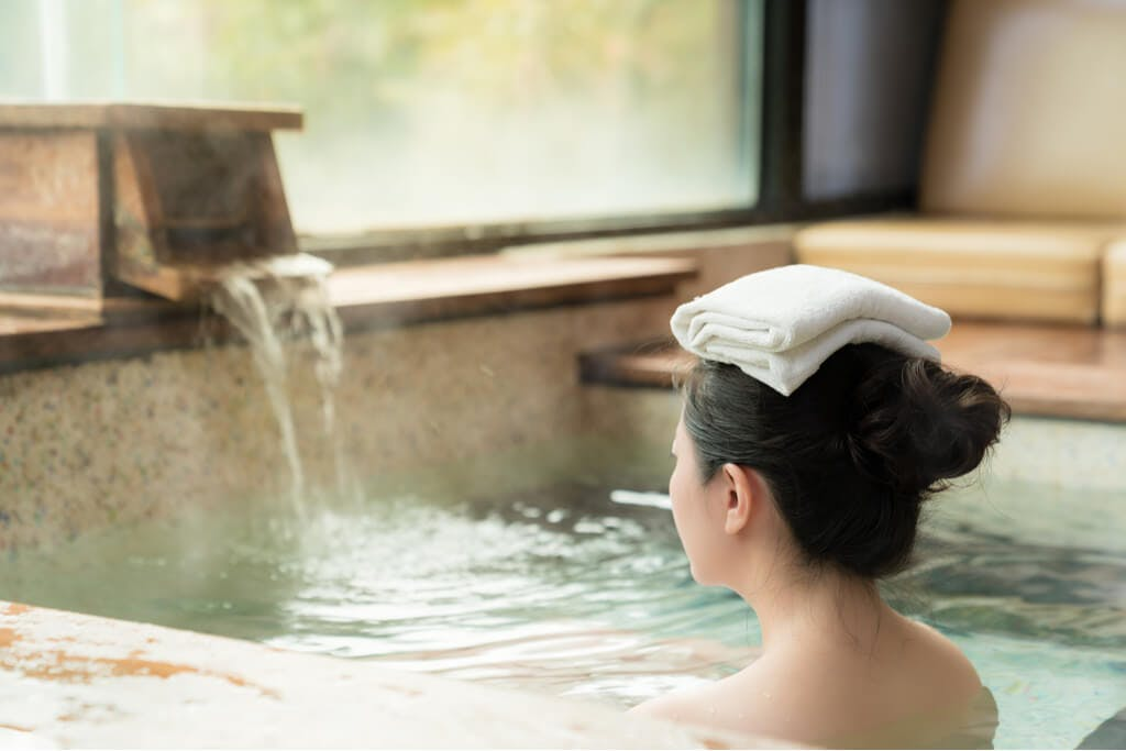 A woman with a towel on her head sits in a sento with a wooden spout pumping in new water