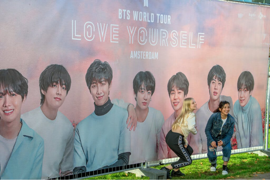 Two young women pose in front a BTS World Tour Billboard