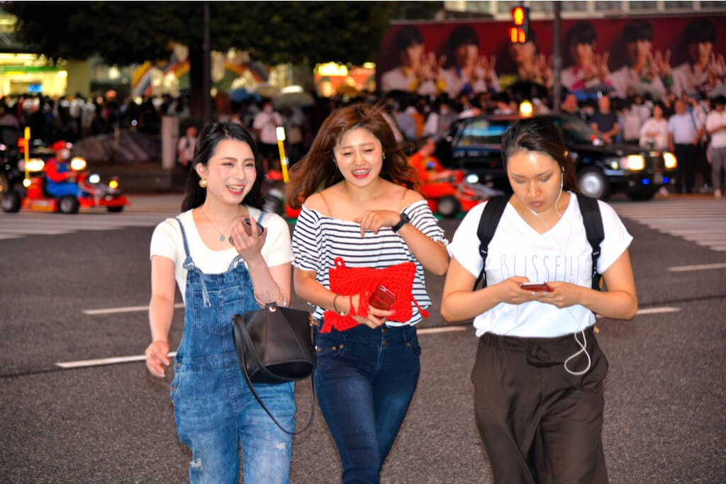 Two young women talking to each other while a third messages on her phone on the streets of Shibuya in front of a Mario Kart tour