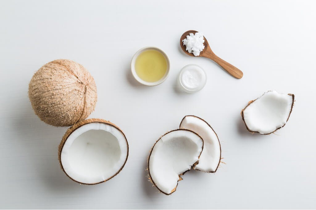Coconuts sit on a table, most of them cracked open, with an oil and cream next to it and a wooden spoon with coconut shavings