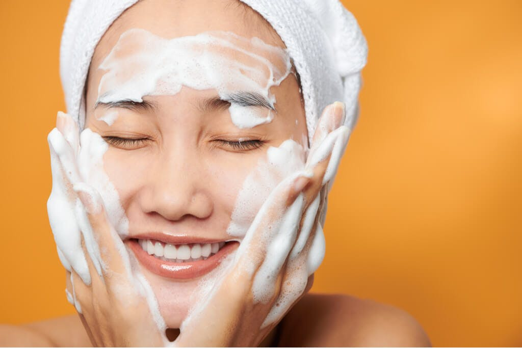 A woman washing her face with a towel wrapped around her face in front of an orange background while smiling