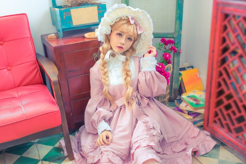 A girl in Lolita-style clothing sits in a room next to a chair and in front of a drawer.