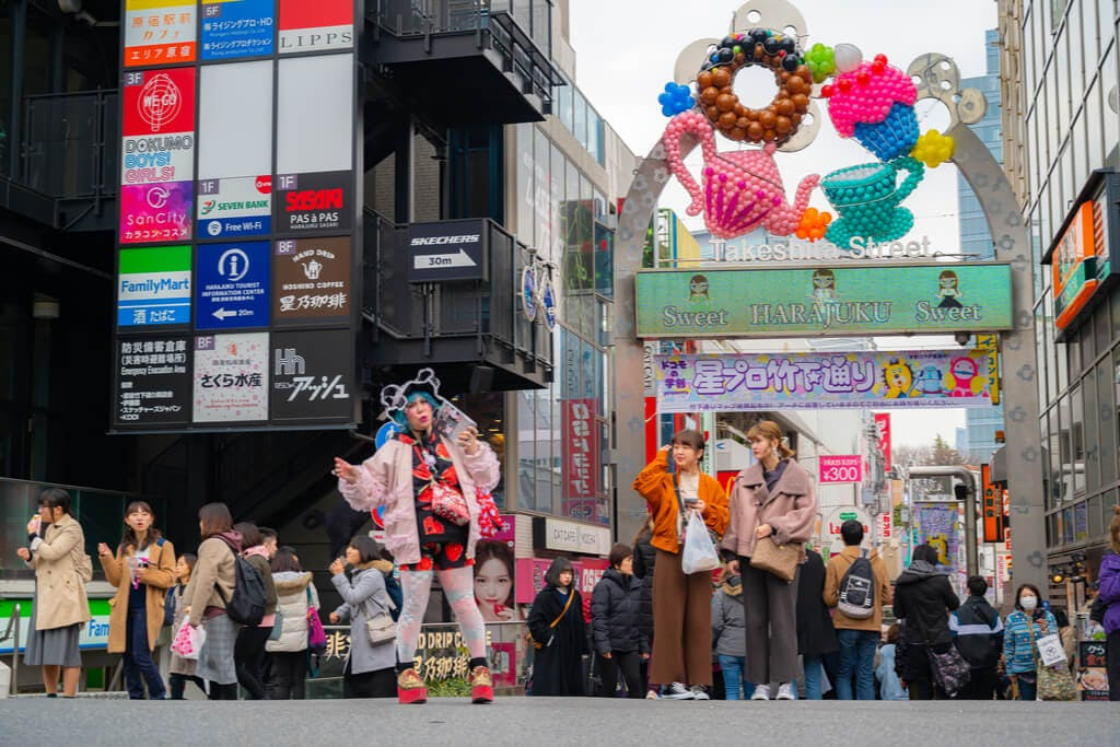 People in front of Harajuku's Takeshita Street with several desserts made of balloons above the takeshita street sign