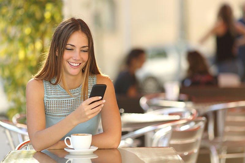 Kvinna ansöker om smslån med mobilen