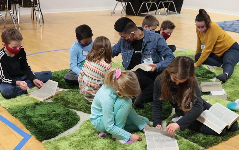 Children surrounding a teacher on a large rug, reading their Bibles.