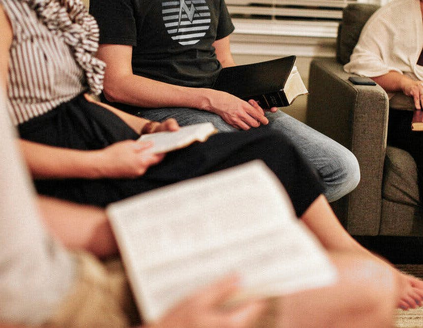 A group of adults with Bibles engaged in discussion within a living room.