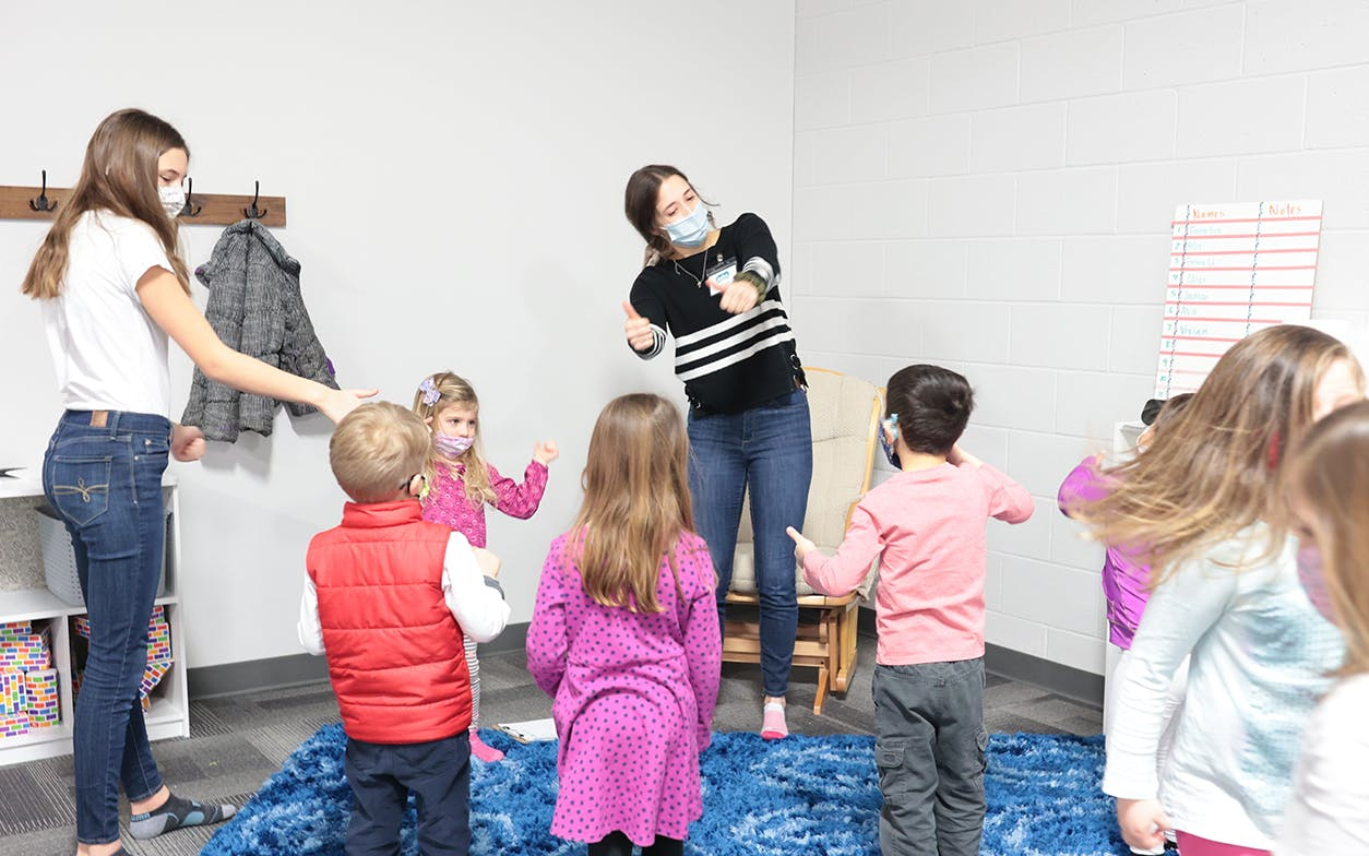 Teachers and children worshiping together with fun movements.