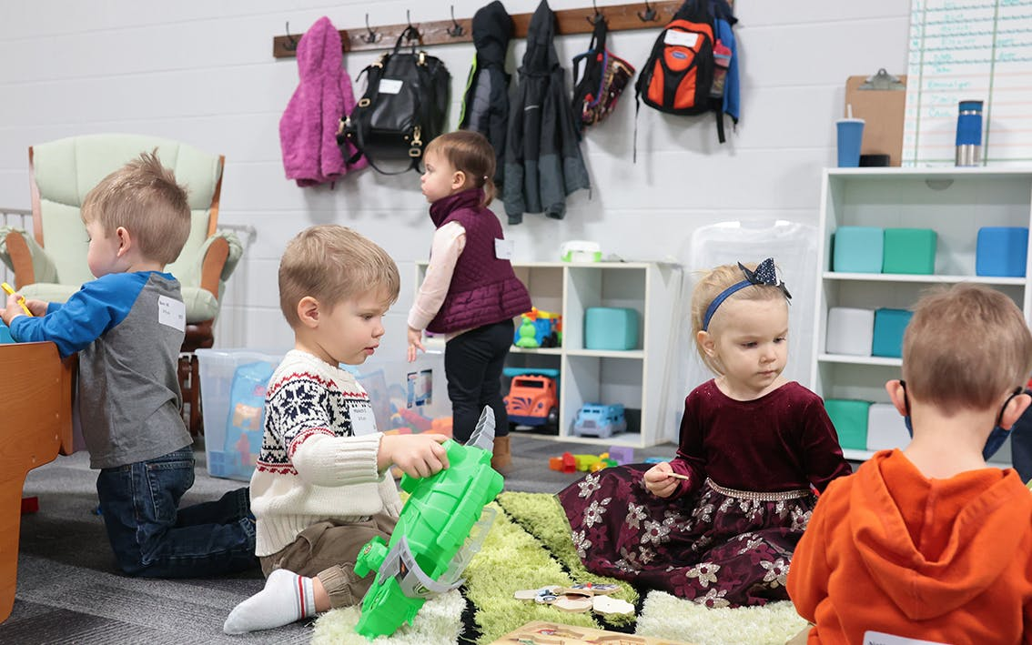 A group of two and three year olds playing together.