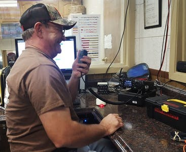 Michael Bentley from Texas smiles and talks on a CB radio.