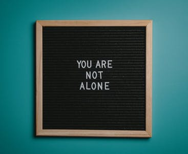 "A board featuring the words ""You are not alone"" on it."