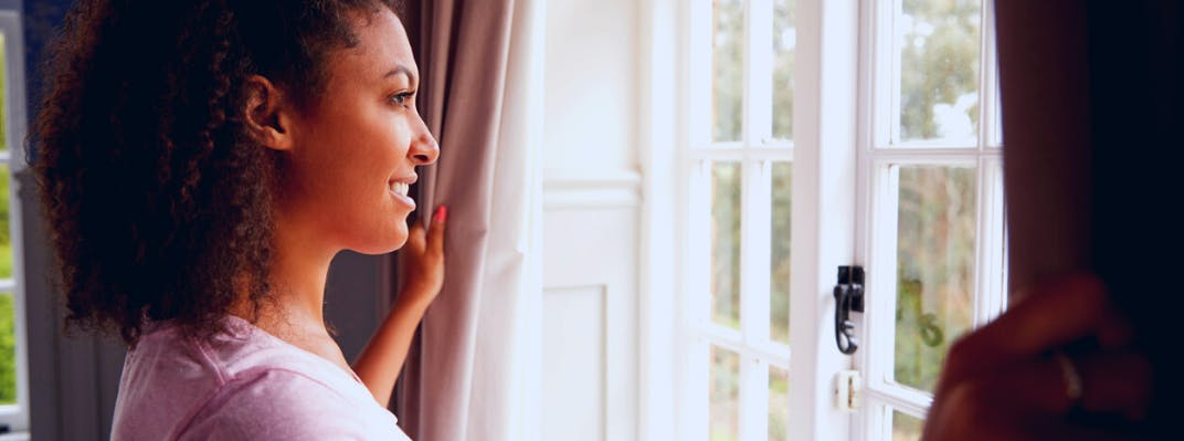 A woman holds open the curtains and looks out a window smiling.
