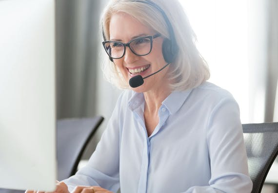 A woman sitting at a computer and wearing a headset smiles.