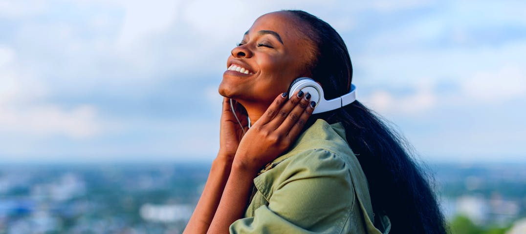A woman sits outside listening to audio on her headphones smiling.