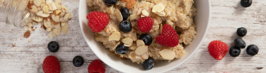 Granola and berries in a bowl with almonds.