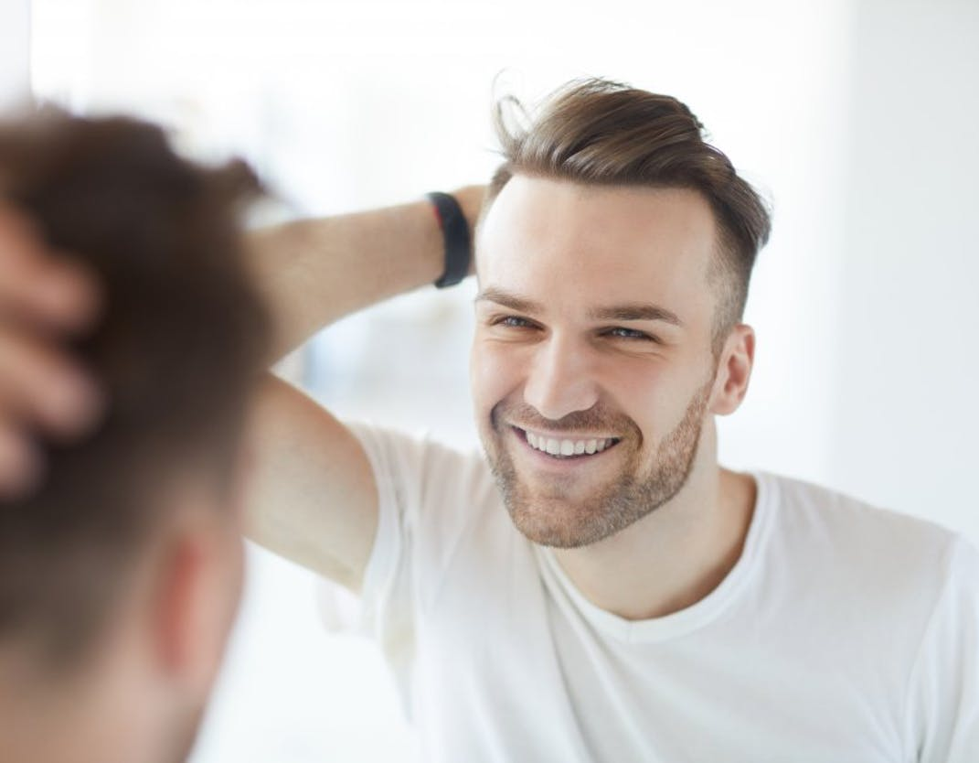 A man runs his hand through his hair and smiles in a mirror.