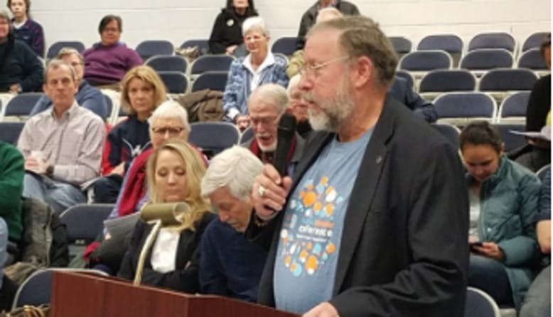 NPF advocate Stephen from Virginia, speaking at a podium in a public forum.