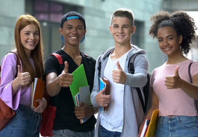A group of young teens smiling and giving thumbs-up.