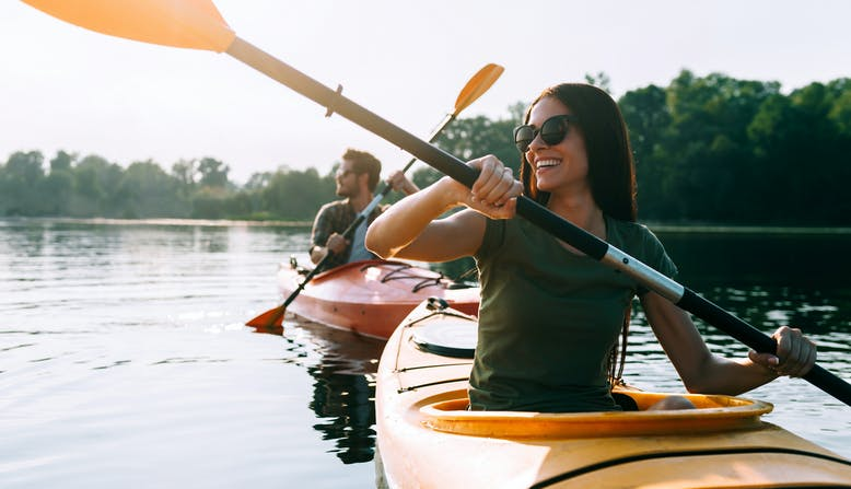 A couple kayak on a lake smiling in the summer.