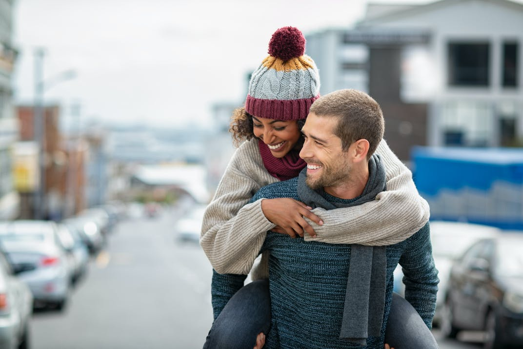 A man gives a lady a piggyback ride, while both are wearing winter clothing.