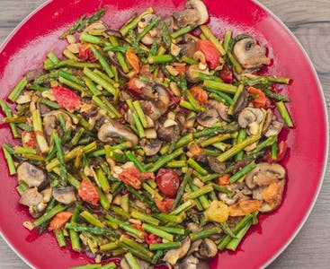 A red plate of tomatoes, mushrooms and green beans.