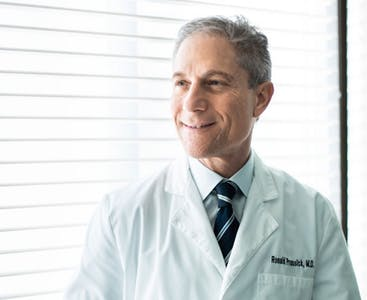 Dermatologist Ronald Prussick smiles while wearing a white coat.