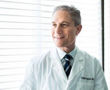 Il dermatologo Ronald Prussick sorride mentre indossa un camice bianco.