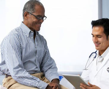 A man sits with his doctor smiling.