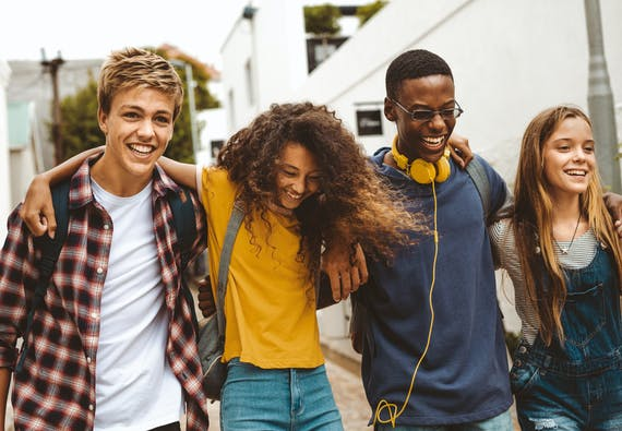 Four teens walking with their arms around each other and smiling.