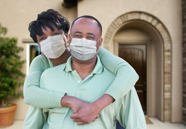 A couple stand together in front of their house smiling and wearing masks.