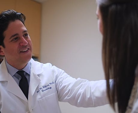 Doctor smiling as he talks with patient