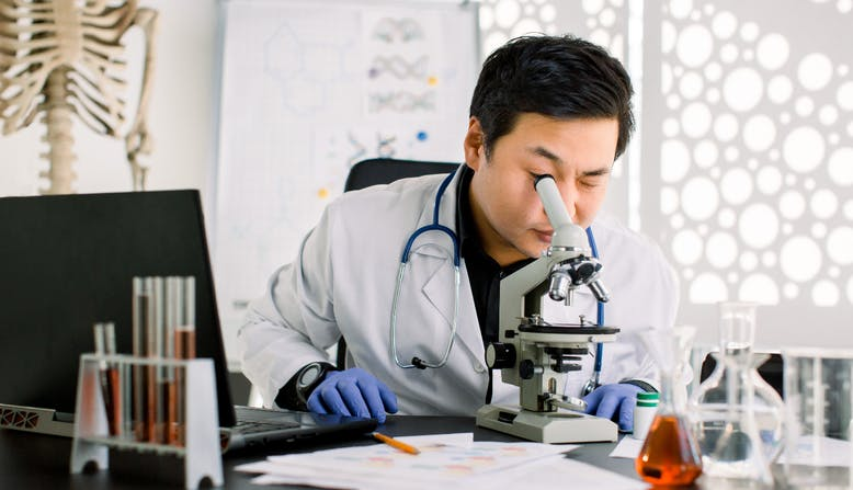 A male researcher looks into a microscope